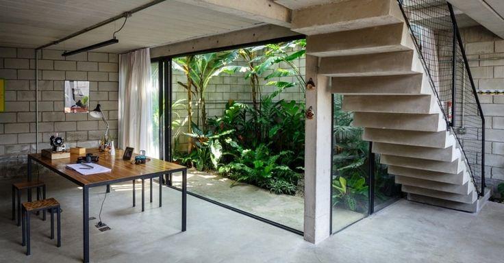com vista para o jardim de inverno: em evidência estilo industrial com blocos de cimento aparente, escada de concreto e peitoril de grade