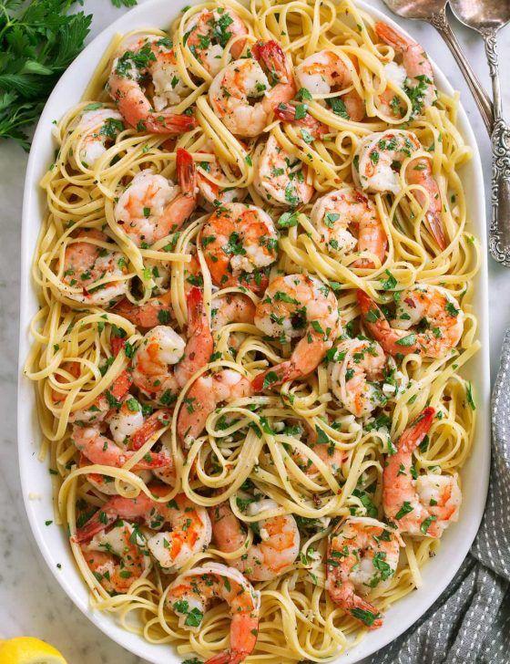 Shrimp scampi on a platter tossed with linguine pasta.