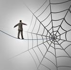 Businessman trap business concept with a tightrope walker walking on a wire leading to a giant spider web as a metaphor for adversity and deception of being lured to new career recruiting.
