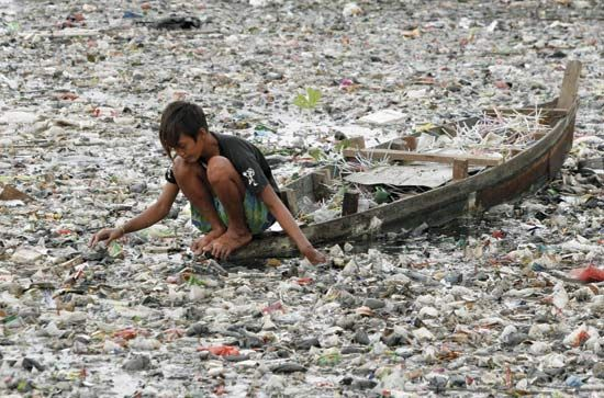 Indonesian boy collects plastic bags from a polluted river in Jakarta; Jurnasyanto Sukarno—Corbis