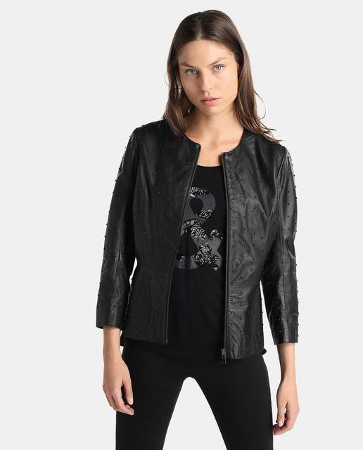 Cazadora de piel en color negro con adorno de tachas. Tiene manga larga, cuello redondo y cierre de cremallera.