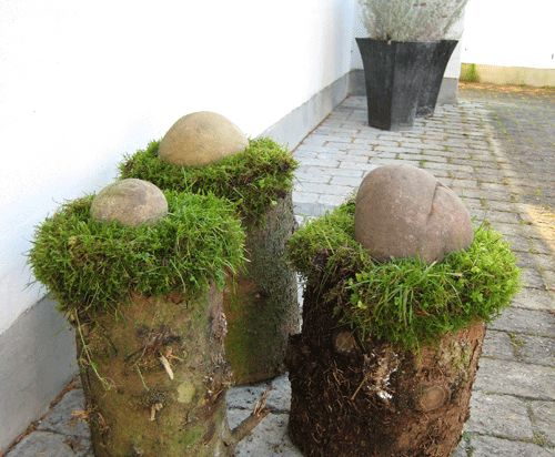 Logs with moss and a stone on top as winter decoration