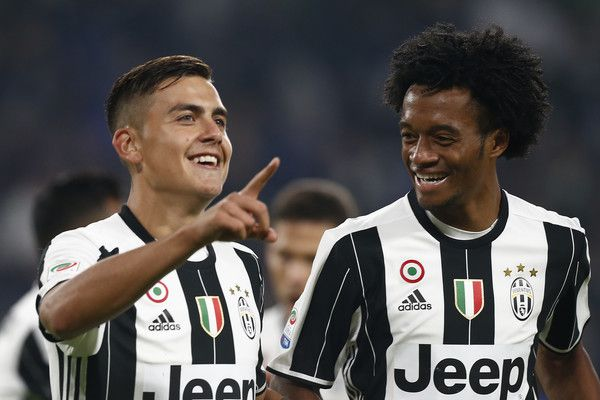 Juventus' forward Paulo Dybala from Argentina (L) celebrates after scoring with Juventus' midfielder Juan Cuadrado from Colombia during the Italian Serie A football match Juventus vs Udinese on October 15, 2016 at the 'Juventus Stadium' in Turin. / AFP / MARCO BERTORELLO
