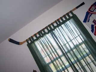 Hockey stick curtain rod. Neat idea for a sports fans bedroom!