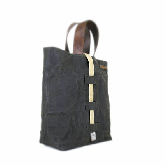 Waxed canvas tote bag with leather straps • Handmade product • Material: drawn, old military hand waxed duffle bag • Size: 40cm/15.7 width, 35cm/13.8 height, 12cm/4.7 depth • Inside there is 1 big pocket with zip and 1 pocket which falls into 2 parts • Its lining is strong canvas • The straps': 33.5cm/13.2 (singly)  In this shop you can find handmade, unique products. I reuse old military truck canvas, dufflebags, and various bags as materials. I select and clean them with extra carefulness…