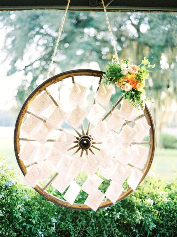 Wagon Wheel Escort Card Display / http://www.deerpearlflowers.com/rustic-country-wagon-wheel-wedding-ideas/