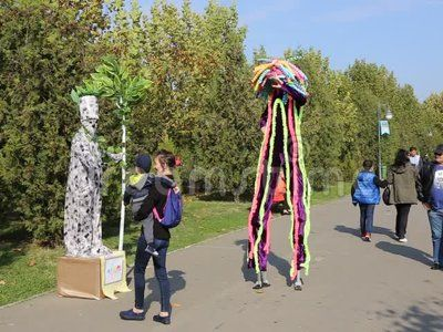 Vivid statue and clown on stilts at LollyBoom Festival 2017  family festival in the Izvor park, Bucharest, Romania.