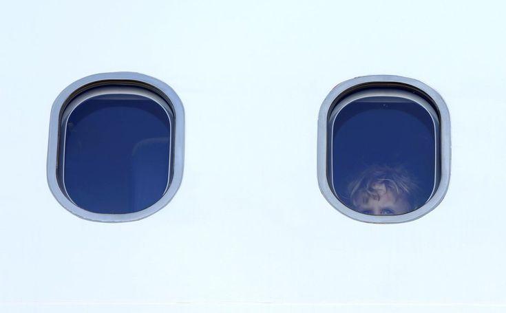 Un niño observa por la ventana de un avión antes de viajar de Tirana a Pristina, desde el aeropuerto de Múnich (Alemania). Unos 90 migrantes procedentes de Albania y Kosovo fueron extraditados después de que su solicitud de asilo fuese rechazada.  MICHAELA REHLE (REUTERS)