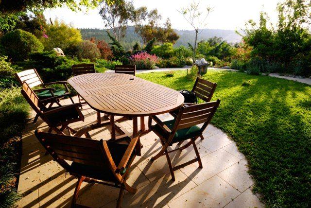 terrasse carrelée donnant sur le paysage, table en teck