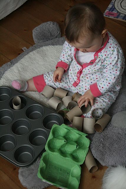 Filling and emptying a cake tin with cardboard tubes and opening and closing boxes.