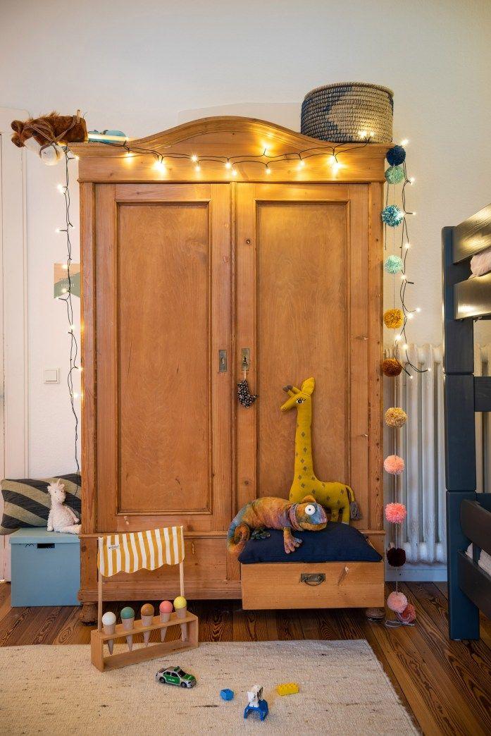 Shop my interior – Das Kinderzimmer – Der Kleiderschrank ist ein Erbstück, verziert mit einer PomPom-Girlande, Lichterkette, Kuscheltieren und ei…