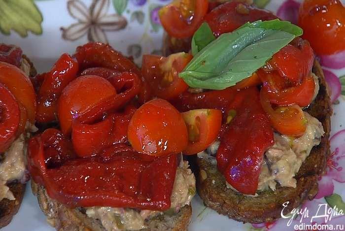 На обжаренный хлеб выложить тунца с оливками и каперсами, сверху поместить запеченный перец с помидорами, украсить замаринованным луком и листьями базилика.