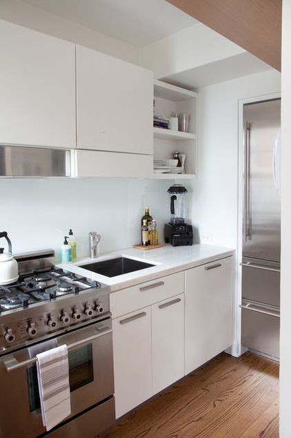 Teeny, tiny 50 square foot kitchen. Compact but efficient. It helps they could inset the fridge into the wall.