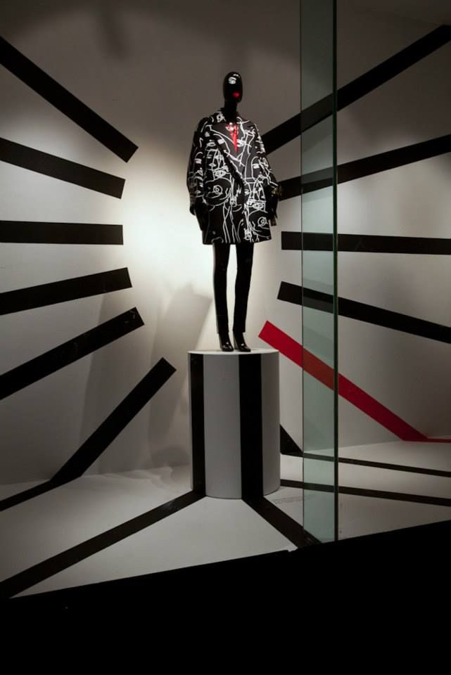Color: Black, White, and Red Balance: symmetrical (formal), Emphasis: the mannequin  in the middle of the display, Rhythm: The lines around the mannequin .
