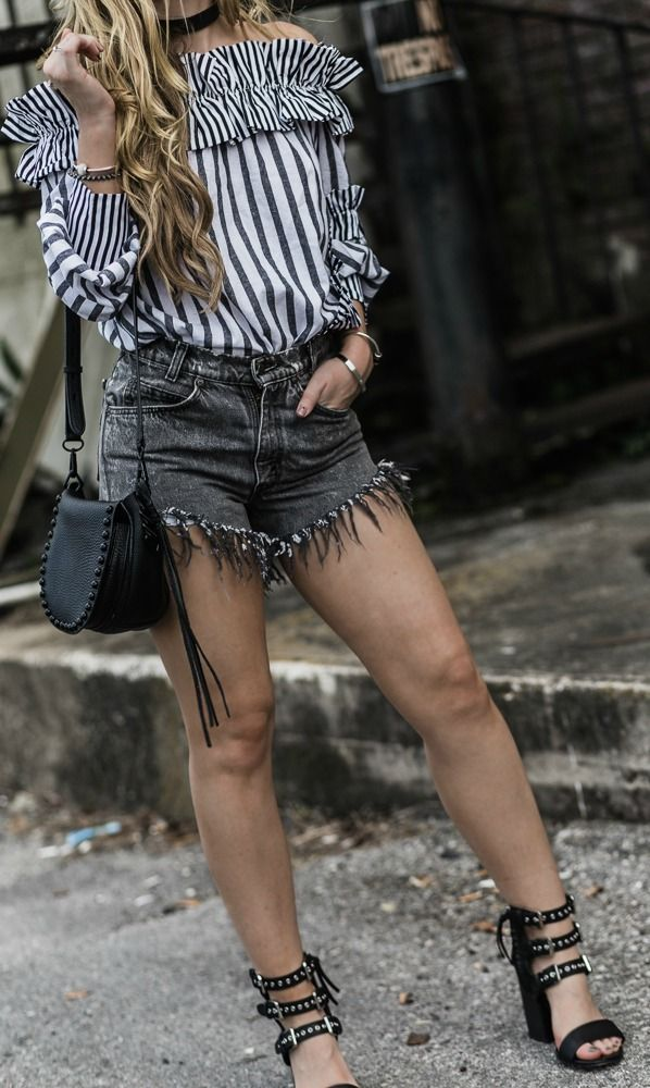 Edgy spring outfit styled with off the shoulder striped top, distressed acid wash shorts, and Dolce Vita block heels