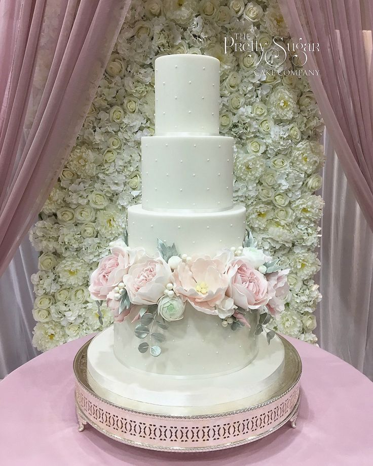Piped pearls wedding cake with palest pink sugar peonies and garden roses against a stunning backdrop of ivory silk flowers