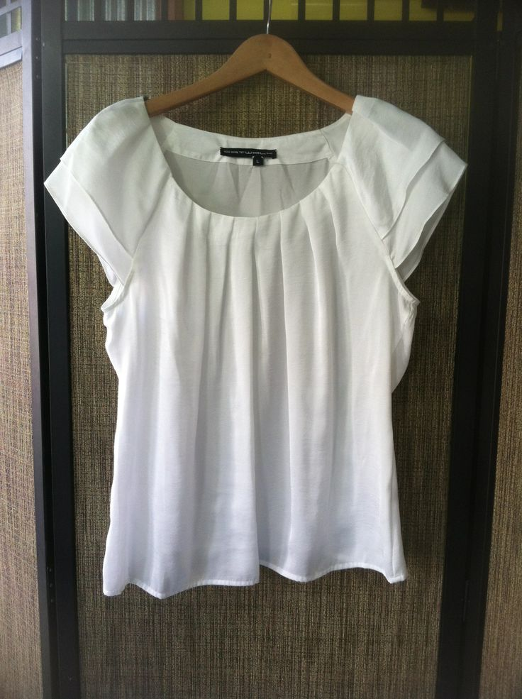 Mini - Feminine pleated neck, flutter, cap sleeve shell. - Color White - Sizes Small, Medium and Large - Price $99.00 Call Us: 646-284-5049