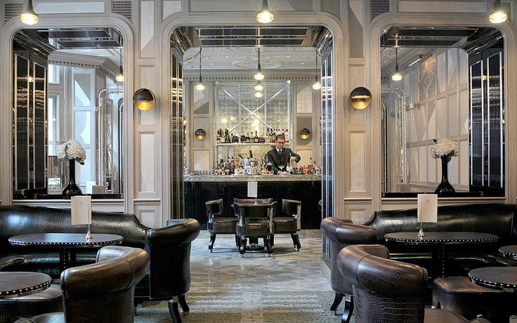 David Collins Studio designed The Connaught Bar, The Connaught London. This multi-award winning bar comprises three rooms featuring degrade leathers, metal studded black leather tables, and silver leaf mirror artwork commissioned by David Collins and panelled in a hand painted hibernian landscape of dusty pink, pistachio green and pale lilac.