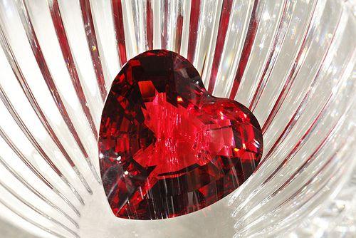 """Still life. Cuore di cristallo rosso dentro un vaso di vetro bianco scanalato. Le ripetute linee delle scanalature sembrano una gabbia per il cuore, che """"vede"""" solo i riflessi indecifrabili della luce esterna, un po' come nel mito della caverna cosmica. A volte la pretesa d'illuminare acceca!"""