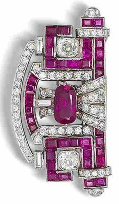 An Art Deco ruby and diamond plaque brooch, circa 1930. The central cushion-shaped mixed-cut ruby between two cushion-shaped diamonds, within a pierced scroll-shaped mount, symmetrically-set with calibré-cut rubies and brilliant, old brilliant, single and baguette-cut diamonds, diamonds, length 5.2cm.