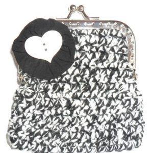 Porta moedas feito em linha barbante nas cores preto e branco. A decorar tem um coração branco em madeira. O fecho é o tradicional fecho da avó. Ideal para guardar moedas ou pequenos cartões.  Tamanho aproximado: 8cm x 9cm Preço: 3€