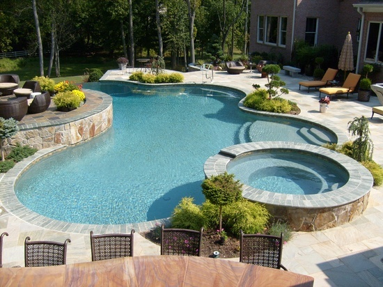 Anthony & Sylvan pool designers bring out the best in your home by working with the natural landscape of your backyard to create a summer oasis.  This freeform in-ground pool features a raised spa, waterfall and bar—perfect for relaxing on hot summer days. #swimmingpool #backyard #pooldesign  http://www.anthonysylvan.com/pools-options.asp
