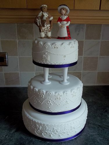 Zimbabwean and Welsh wedding cake. A 3 tier pillared wedding cake with Broderie Anglaise decoration and personalised figures - dressed in Zimbabwean and Welsh national dress. Pretty.