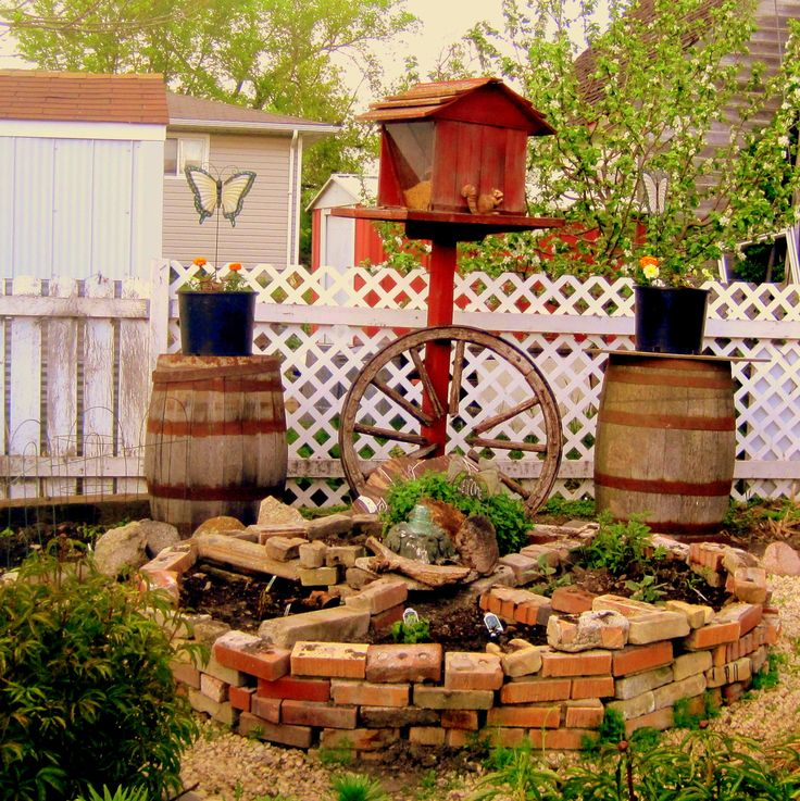 We created herb/medicine wheel from recycled bricks we found at the dump. The wagon wheel by the bird feeder and whiskey barrels carry the southwestern feel from the house to the yard.
