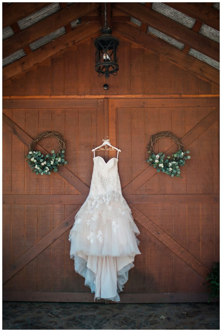 Rustic wedding, barn doors with wreaths, beautiful tiered wedding dress handing on a custom hanger - Simply Bliss Photography - Best of 2017 Arkansas Wedding Photos | Favorite Wedding Details