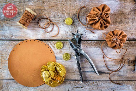Dukatensäckchen selber machen: Ihr benötigt: Kunstleder (oder braunen Stoff) aus dem Stoffladen, Kunstlederband, Lochzange Kuchenteller, Schokoladentaler Kuchenteller als Schablone auf das Kunstleder legen, mit einem Stift umranden und ausschneiden. Mit der Lochzange entlang des Kreises im Abstand von etwa 1 cm Löcher stanzen. Das Kunstlederband durch die gestanzten Löcher fädeln und zusammenziehen, sodass ein Säckchen entsteht. Dukatensäckchen mit Goldtalern befüllen und zuschnüren.