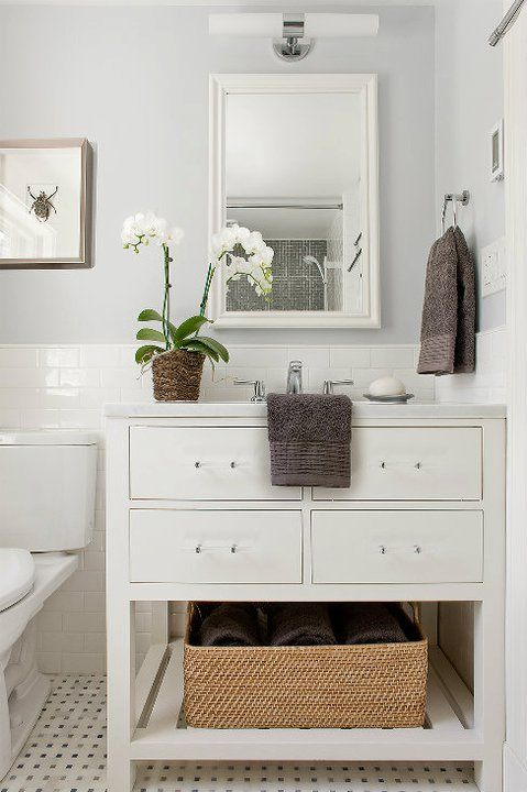 Clean and classic bathroom with pale gray walls, white subway tile backsplash and marble basketweave tiles floor. Restoration Hardware Hutton Single washstand with marble top, white beveled mirror and polished nickel double sconce. Dark gray bathroom towels, woven bathroom storage basket and orchid.