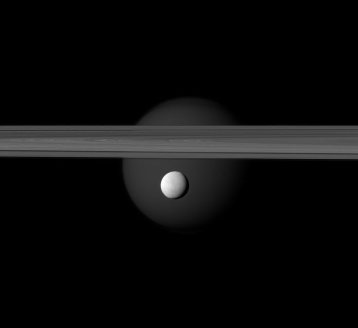 A brightly reflective Enceladus appears before Saturn's rings, while the planet's larger moon Titan looms in the distance.: Planets Largest, Planets Larger, Bright Reflection, Larger Moon, Largest Moon, Moon Titanic, Saturn, Moon Enceladus, Stars Moon Spac