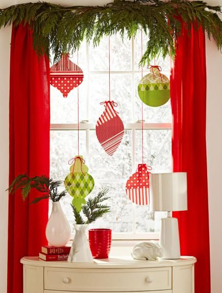 Midwest Living - Red and green scrapbooking paper in fun patterns adorns shapes cut from poster board. Glue three papers onto each ornament. Punch a hole at the top, then hang them on red cording or yarn taped to the top of the window. A valance of live greens finishes the display.