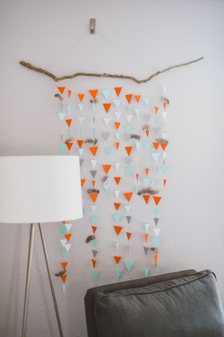 Modern tripod lamp, and DIY sewn paper triangle and feather garland wall hanging from our woodland adventure themed nursery in grey, white, orange, and mint.