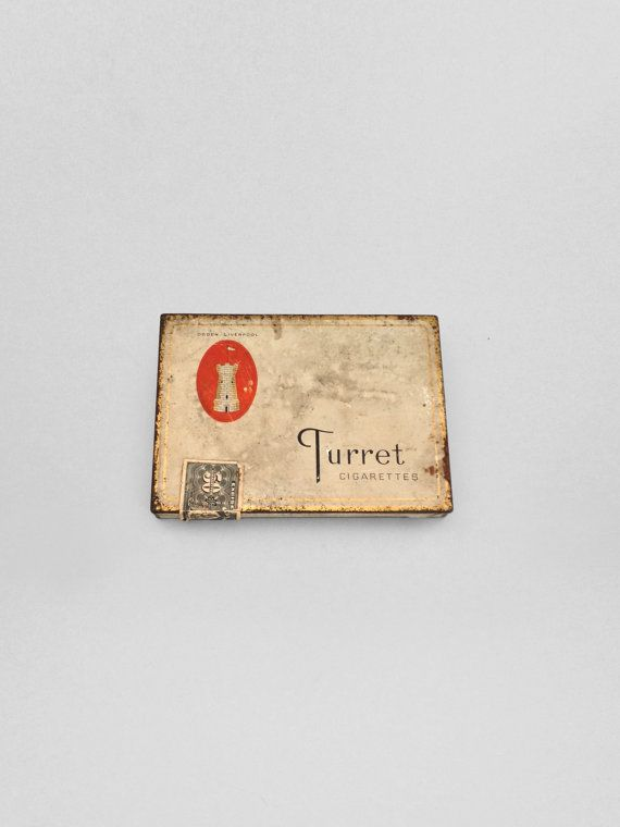 "This cigarette tin for Turret brand cigarettes features a white case with gold trim and castle turret logo reading "" Ogden, Liverpool"" and a tarnished patina to complete the medieval chic look."