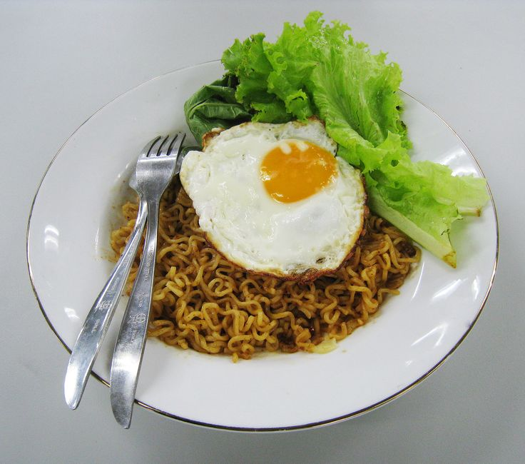 Indomie Mie Goreng Iga Penyet (squeezed rib) flavour. Indomie brand instant noodle, mie goreng (fried noodle), served with fried egg and vegetables. Served in Jakarta, Indonesia.