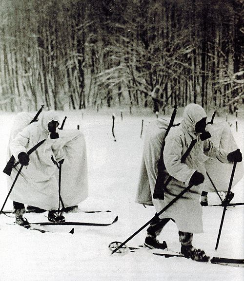 Finnish infantry equipped with gas masks and white camouflage advancing on cross-country skis during the Battle of Suomussalmi, 1939-1940. #Winter War