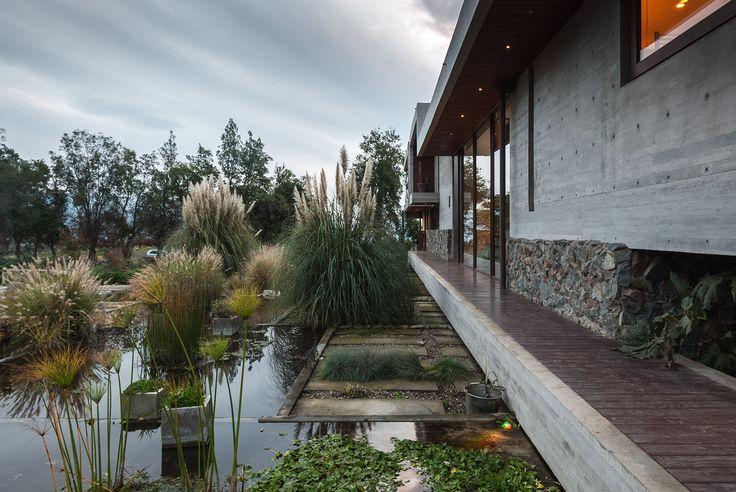 Moderne 'warme' architectuur door waterpartij en bijpassende beplanting.