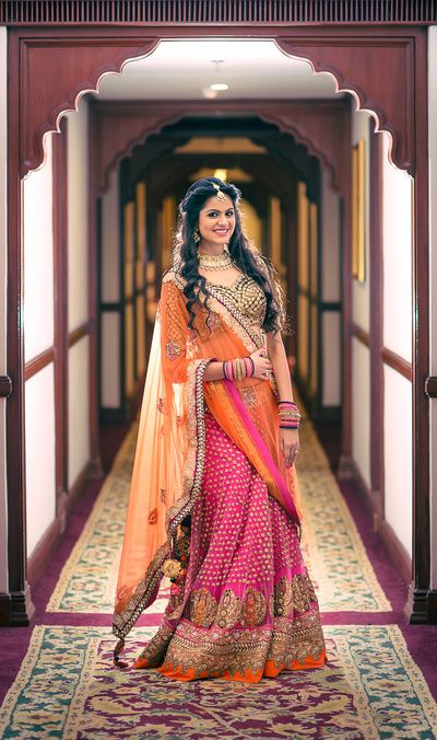 pink and orange lehenga, twisted hair style, gold embroidery, orange net dupatta