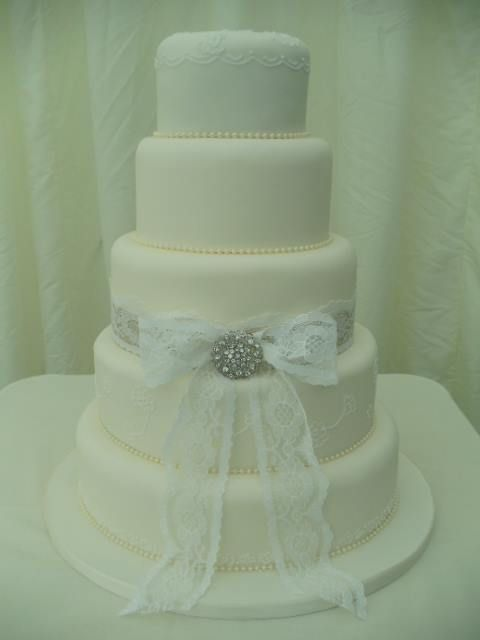 Delicate hand piped lace on this oval shaped wedding cake.