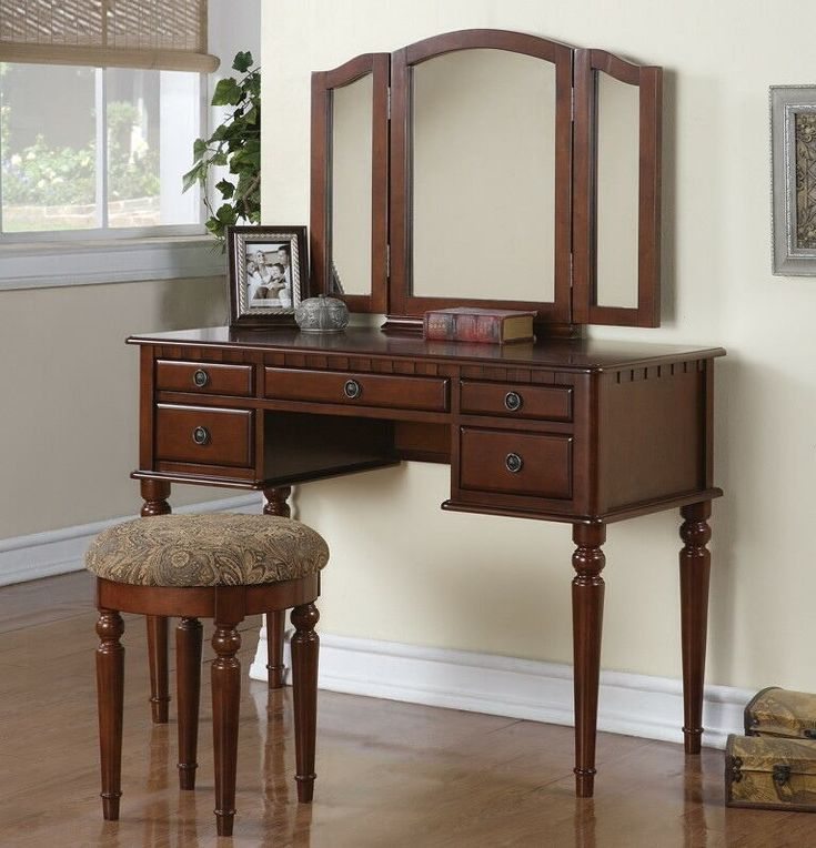 """3 pc Cherry brown finish wood make up bedroom vanity set with curved legs stool and tri fold mirror with multiple drawers. This set comes with the Vanity table with multiple drawers, Tri fold Mirror and the vanity stool. Measures 43"""" x 19"""" x 54"""" H. Some assembly required. Also available in other finishes"""