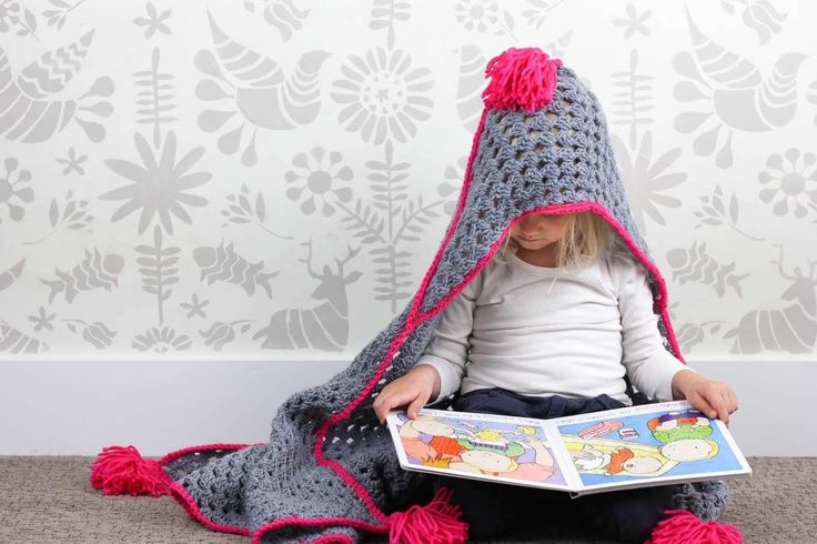 """Based on a large granny square, the """"Granny Gives Back"""" crochet hooded blanket pattern makes an easy and inexpensive project to donate to children's charities. The oversized hood and playful tassels will give any kid a safe, warm place to escape to. Click for the free pattern using Lion Brand Pound of Love yarn!"""