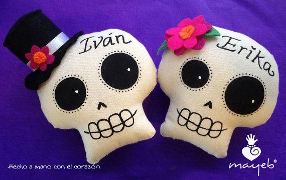 Hermosa pareja de calaveras de manta pintadas a mano.  Nombres en caligrafía.  12 cms de altura, ideal para la ofrenda o de decoración. Tiene cordón para