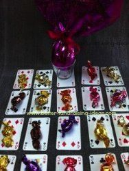 Simple Fundraiser- double decker - have two packs of same cards - lay down one pack and put prizes on top most have boobie prizes such as sweets, balloons, party favours but one or two have big prizes like box of chocolates or money or bubble bath. People buy a card from corresponding down turned deck, they then turn card over and match to upturned deck to win that prize
