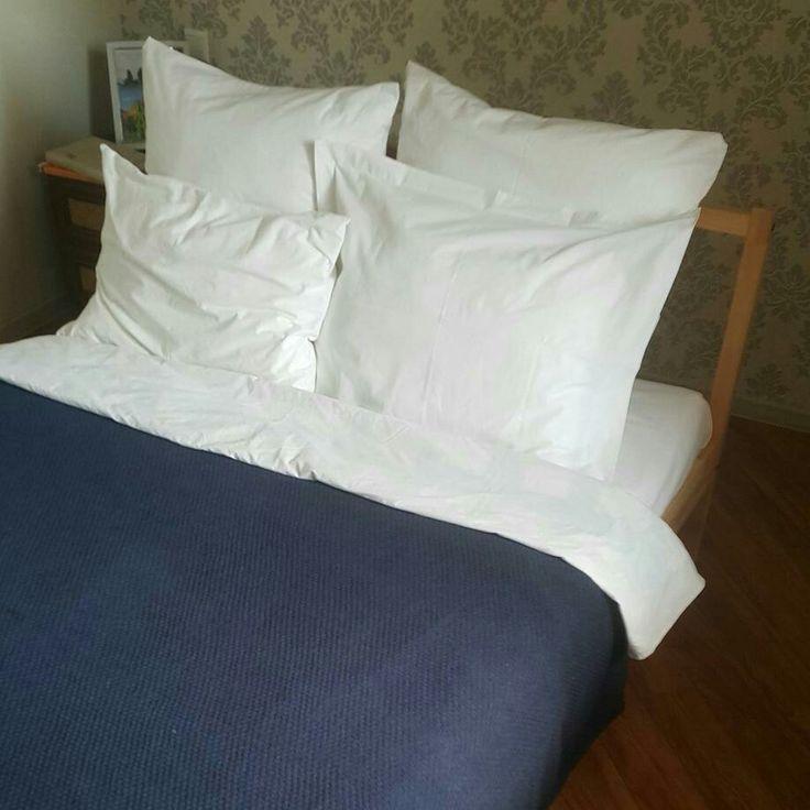 Белое постельное белье и вязаный плед джинсового цвета