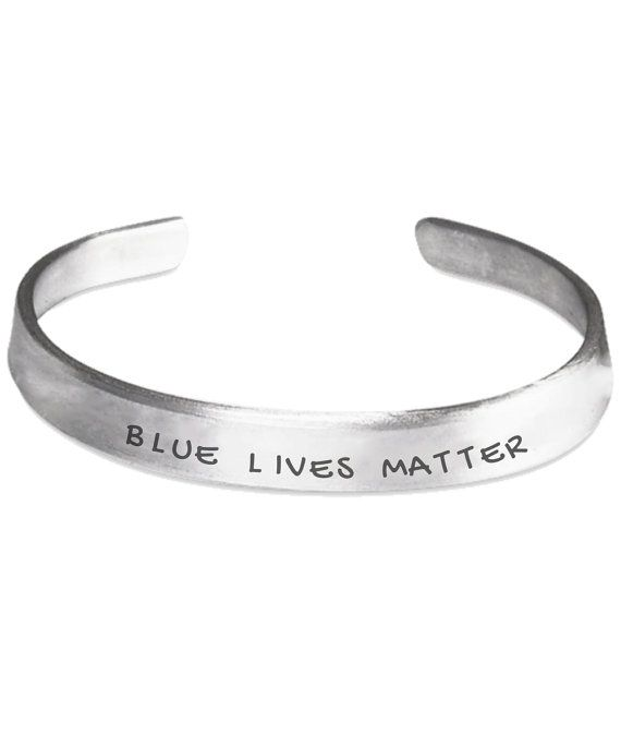 Support law enforcement with this Blue Lives Matter Hand Stamped Bracelet.  * One size fits all. This Police Family Bracelet fits almost everyone upon arrival. It can be easily bent by hand to adjust and fit even the largest wrist.  * Every Cuff Bracelet is handmade in the USA so every piece will be totally unique. There will be slight variations in alignment, font, and depth of stamp from the mock up and the finished product you receive.  * Made from 100% hand polished 1100 Pure Aluminum…