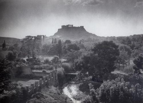 Εκεί που σήμερα ανεβοκατεβαίνει η οδός Καλλιρόης. Τα νερά του χιλιοτραγουδισμένου Ιλισσού φωτίζονται από τον ήλιο, η βλάστηση είναι παραδείσια και η πρωινή πάχνη αγκαλιάζει την πόλη (περίπου 1910)