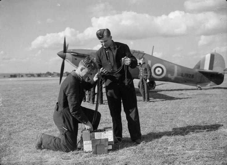 """Armourers prepare ammunition belts for Hurricane Mk I DU-J of No 312 Squadron RAF at RAF Duxford in September 1940. One of the oldest Hawker fighters in frontline service, the fabric-winged aircraft was flown by P/O Alois """"Amos"""" Vašátko of Yellow Section on 8 October, when the 32-year-old Czech scored their first victory, sharing a Ju 88 over Liverpool with F/L Denys E """"Kill 'em"""" Gillam and Sgt Josef Stehlík."""