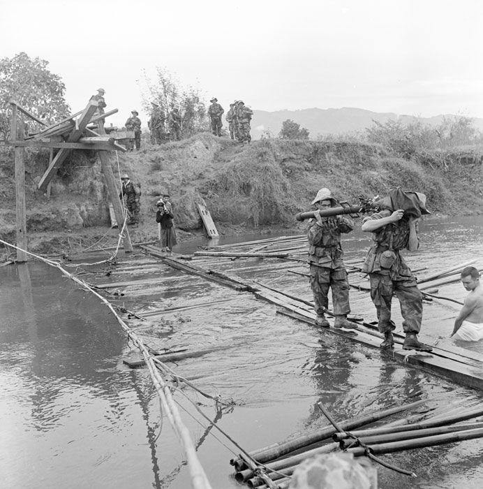 """Transportant un canon de 75 mm SR (Sans Recul), deux légionnaires du 1er BEP (Bataillon Étranger de Parachutistes) franchissent la Nam Youm sur un pont de fortune, à Diên Biên Phu, lors de l'opération """"Castor"""". Date : Novembre 1953"""