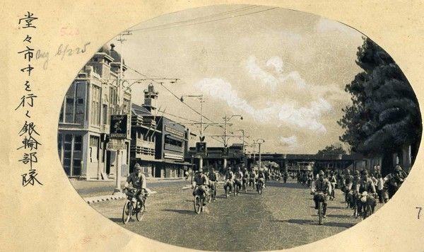 Een foto uit een album van een Japanse soldaat  dat een beeldverslag van de Japanse opmars op Java in maart 1942 geeft.  De vertaling van het bijschrift luidt: Een rijwielbrigade rijdt dapper en moedig door de stad (Soerabaja).